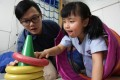 Occupational therapist Steve Chan (left) and six-year-old Sasa Lao at the Rainbow Project's learning centre on Sai Yuen Lane in Western. Photo: Dickson Lee