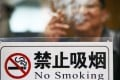 A man lights up in clear sight of a no-smoking sign in Jiangsu province.  Photo: Imaginechina