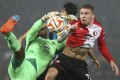 Feyenoord's goalkeeper Kenneth Vermeer loses the ball as he jumps with Sevilla's Alejandro Arribas, rear, and Feyenoord's Sven van Beek, right. Photo: AP