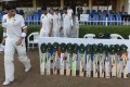 Pakistani cricketers walk past bats and caps placed outside the Pakistani dressing room to match the campaign #putoutyourbats launched in respect of Australian cricketer Phillip Hughes who died. Photo: AFP
