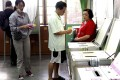 Voters cast their ballots at a polling station in New Taipei City. The KMT held on in the city, a rare highlight for the party. Photo: EPA