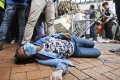 An injured protester lies on the ground during clashes on Monday. Photo: AP
