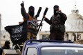 Fighters from al-Qaeda's Nusra Front gesture as they drive through villages in Syria's Idlib countryside on Tuesday, which they claim to have seized from Syrian rebels. Photo: Reuters