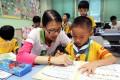 Hang Seng team volunteer Kitty Lai Man-ying helps primary school pupil Lee kit-ho. Photo: Edward Wong