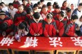 """Students sign their names on a banner with the words """"Constitution spirit"""" during an event to mark China's first Constitution Day in a school in Binzhou city. Photo: AP"""