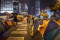 Pedestrians and protesters walk on a section of Harcourt Road, a multi-lane highway through the heart of the financial district currently blocked by pro-democracy protester barricades and hundreds of tents. Photo: AFP