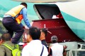 Airport officials unload coffins of two policemen at Sentani airport in Jayapura, Papua, on December 4, 2014. Photo: AFP