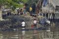 Bangladeshi villagers collect oil after tanker sank.Photo: AFP