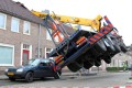 A truck hangs in the air after the crane toppled over onto the house in Ijsselstein. Photo: EPA
