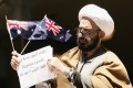 Siege gunman Man Haron Monis is pictured in 2009, bound in chains and holding an Australian flag outside a Sydney court, after having been charged with seven counts of sending harassing letters to families of Australian soldiers. Photo: EPA