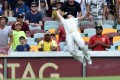 Australia's David Warner dives as he tries to take a catch on the boundary on day four of the second test against India. Photo: AFP