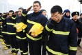 Firefighters salute and cry as they mourn for fellow firefighters, who were killed after a building collapsed during a fire, in Harbin, Heilongjiang. Photo: Reuters