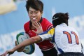Hong Kong's Aggie Poon Pak-yan, who came to rugby by way of the national sprint team, fends off a tackle from Liliya Bazyaruk of Kazakhstan during the 2014 Asian Games. Photo: Nora Tam/SCMP