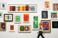 """An employee poses with paper cut outs from the """"Henri Matisse: The Cut-Outs"""" exhibition at the Tate Modern gallery in London. Photo: Reuters"""