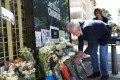 A French official places flowers at the entrance of the French embassy in Bogota, Colombia. Photo: Reuters