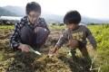 James Lam shows youngster Javas Lo Ho-yin some farming fundamentals in Tse Uk Tsuen. Photo: Dickson Lee