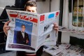 """An Iranian man reads a copy of the January 13 edition of the reformist daily newspaper """"Mardom-e Emrooz"""" featuring a photo of George Clooney with a headline reading """"I am Charlie, too"""". Photo: EPA"""