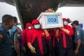 Indonesian rescue personnel unload a coffin bearing a body recovered from the underwater wreckage of the ill-fated AirAsia flight QZ8501. Photo: AFP