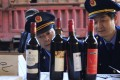 Police officers check bottles of confiscated fake wines. Photo: Reuters