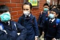 It's all masks for these children outside Hennessy Road Government Primary School in Wan Chai as fears mount over flu outbreaks. Photo: Dickson Lee