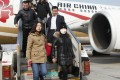 An alleged 'economic fugitive' (wearing mask) arrives in China last week after 10 years on the run in Italy. Photo: Xinhua