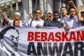 Supporters of Malaysian opposition leader Anwar Ibrahim hold a banner  reading 'Free Anwar' during a court case against Foreign Affairs Minister Anifah Aman in the Duta Court Complex, Kuala Lumpur on Febuary 17, 2015. Photo: EPA