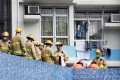 Firefighters arrive at the scene after the elderly man carrying a baby jumped from the apartment building. Photo: SCMP Pictures
