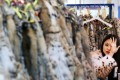 A camera-shy exhibitor wears a fur coat at her stand during the opening day of the fair at the Convention and Exhibition Centre in Wan Chai yesterday. Photo: David Wong