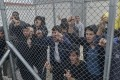 Migrants shout behind a fence at a detention camp. Photo: AP