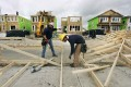 Construction workers build homes in Calgary. Buyers are hoping for a real estate slump. Photo: Reuters