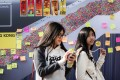 """Two girls walk past a billboard depicting the """"Lennon wall"""" during the Occupy Central movement. The city has been plagued by a culture of suspicion that divides its people into polar opposites and sometimes blinds them to common sense. Photo: AFP"""