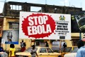 """People walking past a billboard reading """"Stop Ebola"""" in Freetown. Photo: AFP"""