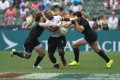 Fiji's Jerry Tuwai runs into trouble in the Cup quarters against England. Photos: Nora Tam/SCMP