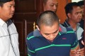 Zulkipli Abdullah (left) is escorted to the high court in Sarawak. He was found guilty of stabbing two foreigners dead. Photo: Reuters