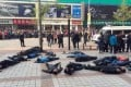 The taxi drivers lie unconscious outside the shopping mall in Wangfujing. Police said they were out of danger. Photo: SMP Pictures