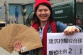 Li Tingting poses with letters and a poster requesting more women's toilets. Photo: AP