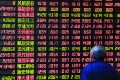 A solitary investor eyes stock prices at an electronic board in Shanghai, China. Photo: Reuters