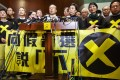 Pan-democratic lawmakers speak to the media after walking out on Chief Secretary Carrie Lam as she launches the government's political reform package in Legco. Photo: EPA