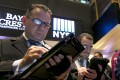 A trader on the floor of the New York stock exchange jots down orders as all US indices lost ground during Thursday's session. Photo: AP