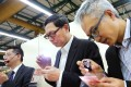Monetary Authority chief Norman Chan (centre) and executive director monetary management Howard Lee inspect notes. Photo: SCMP