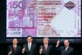 Hong Kong Monetary Authority officials pose beneath the 150th anniversary bank note. The territory's de facto central bank posted huge forex losses and needs to switch strategy, currency traders said. Photo: May Tse