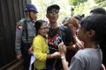 Activist Than Shwe (centre), who protested in front of the Chinese Embassy in Yangon against a Chinese-backed copper mine project, is hugged by crying members of his family. Photo: AP