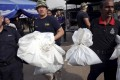 Policemen carry bags with human remains found at the site of trafficking camps. Photo: Reuters