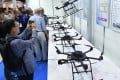 Visitors gather in front of an exhibition booth displaying recent models of drones during the International Drone Expo in Tokyo on May 20, 2015. Photo: AFP