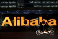 People ride a tandem bike past Alibaba Group's headquarters in China as Ali Pictures, a unit of the e-commerce giant, will raise HK$12.11 billion for media investment opportunities. Photo: Reuters
