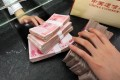 Chinese yuan are handed over to a customer at a bank in the country as the euro marched higher against the yuan and the US dollar. Photo: AFP