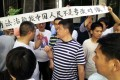 Tang Jingling's supporters, some in T-shirts bearing his photo, raise a banner outside court in Guangzhou yesterday. Photo: Mimi Lau