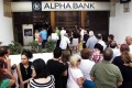 People queue to withdraw money from an ATM outside a branch of Greece's Alpha Bank in Athens, Greece on Sunday. Photo: EPA