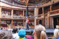 People watch a stage production at The Globe in London.