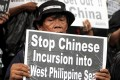 A protester holds a placard during a rally over the South China Sea disputes with China, outside the Chinese Consulate in Makati City, Metro on July 10, 2015.    Photo: Reuters